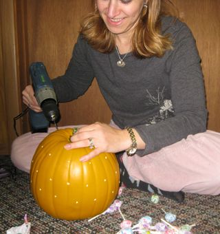 Amy using power drill to make awesome halloween pumpkin